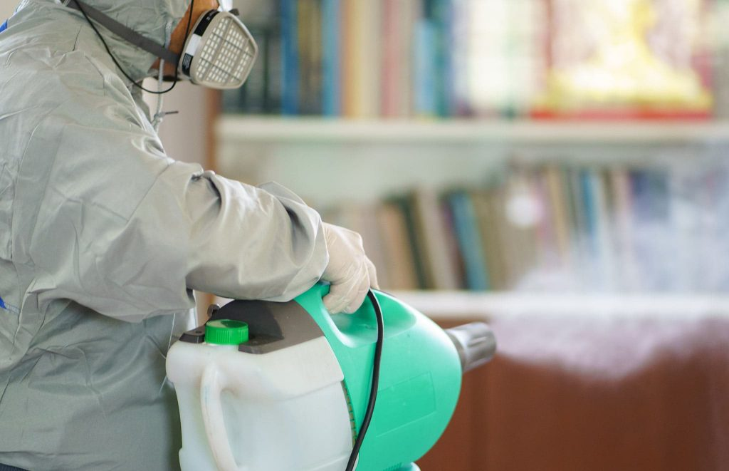 A worker using an electrostatic sprayer