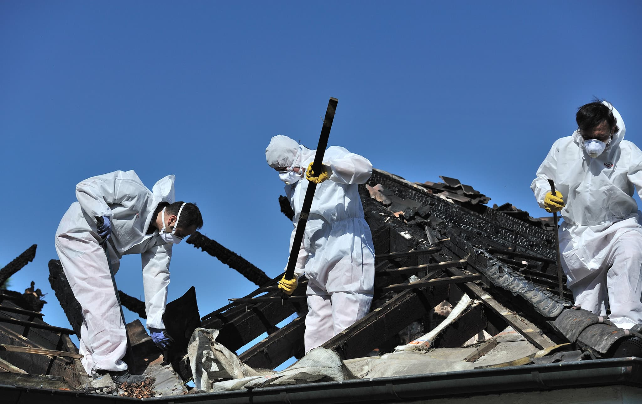 Men working on the roof of a fire-destroyed building